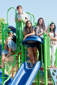 Five teenagers outside on jungle gym.